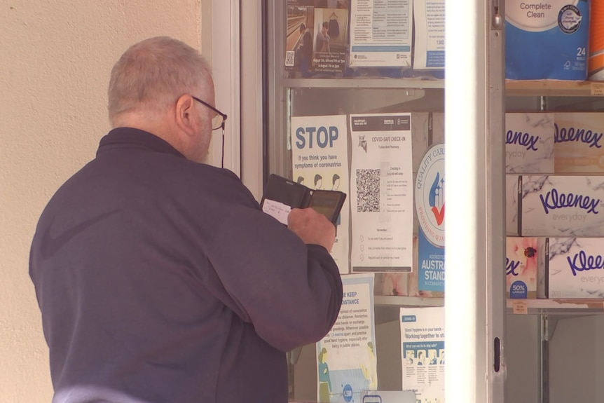 A man holding a mobile phone up to a QR code on a pharmacy window