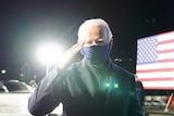 Joe Biden in a face mask saluting