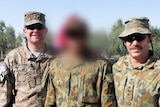Three men in army fatigues standing together, the middle has his face blurred completely