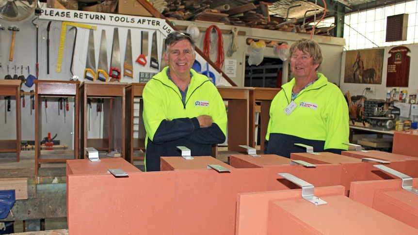 Two men are wearing yellow high vis jumpers are standing in a wood work shop behind a table of nest boxes