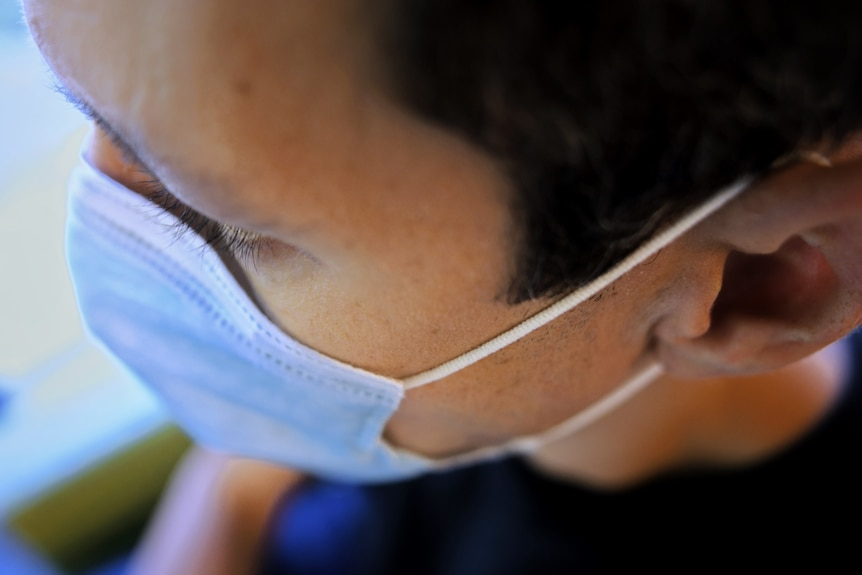 The side of a man's head showing his face mask string wrapped around his ear
