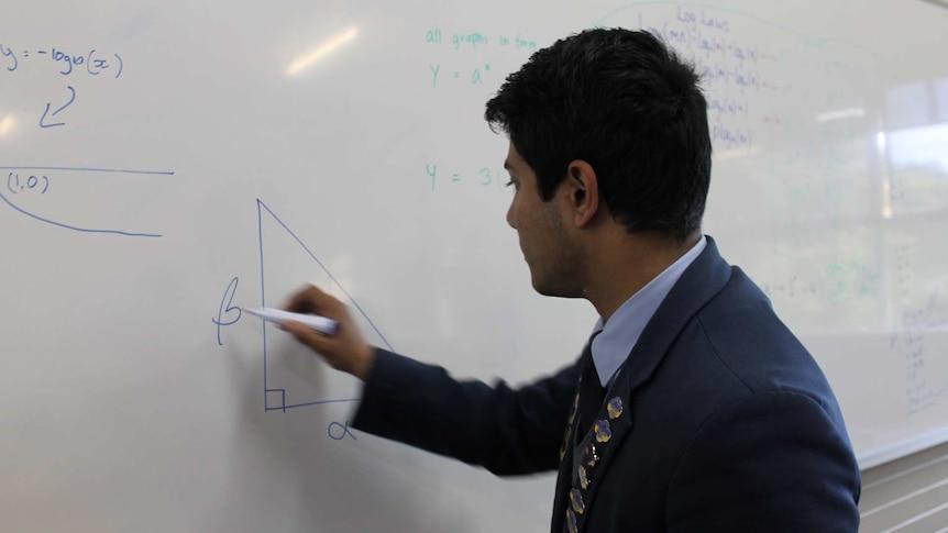 A 17-year-old boy writing on a white board. He's wearing a navy blue school uniform.