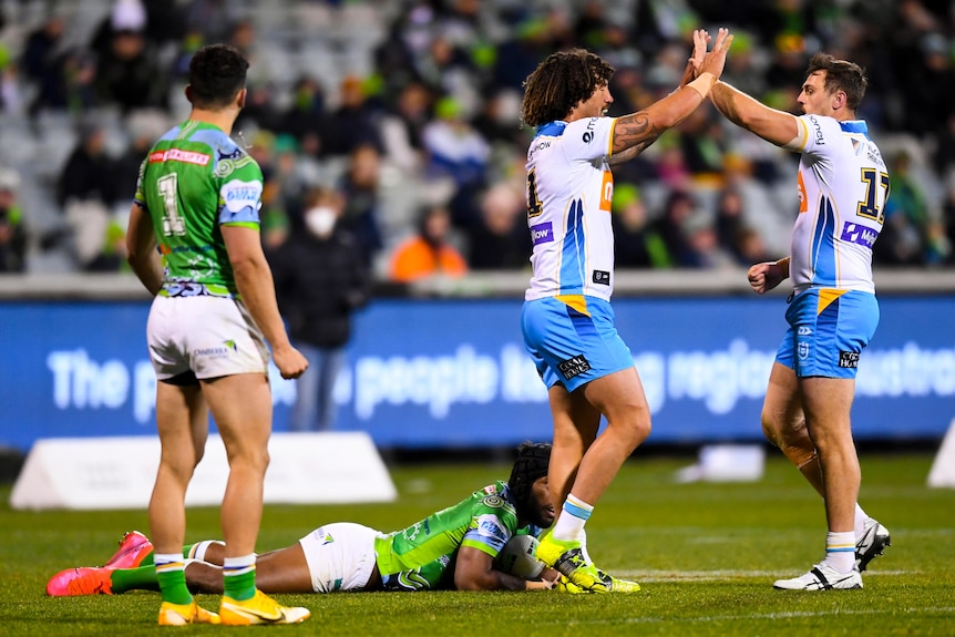 Two Gold Coast NRL players high five each other as Raiders opponents look on.