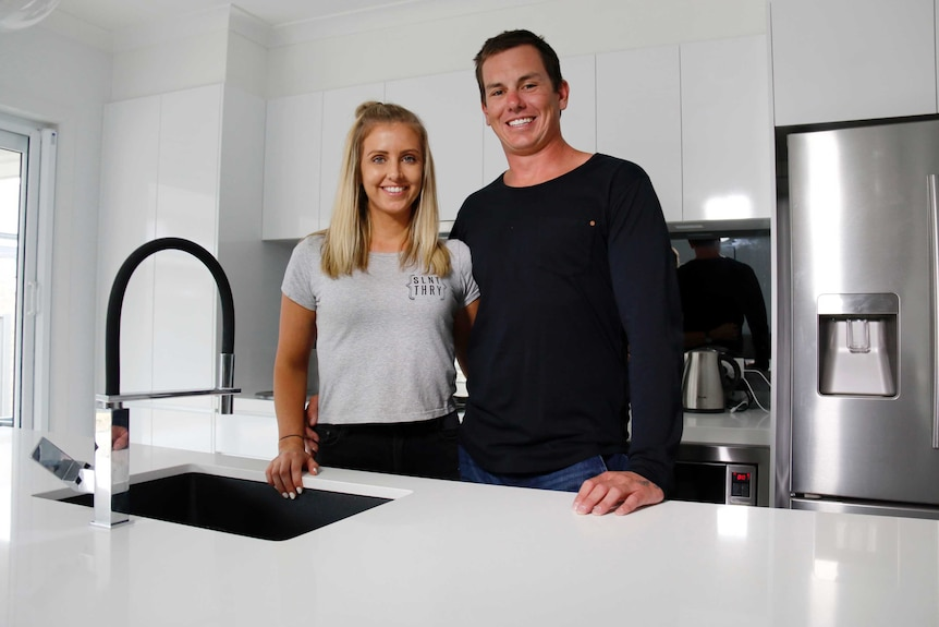 A woman and a man stand in a kitchen.