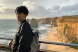 A young Chinese man standing in front of the Twelve Apostles.