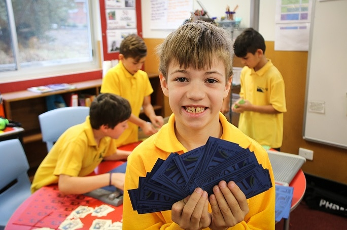 A student from Reservoir East Primary School holds up his class bank notes as part of a finance program.