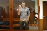 A man gives a peace sign with his right hand as he stands in a glass box dock inside a court with two guards nearby