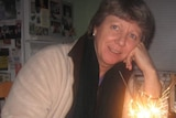 Dianne sits in front of a cake with sparklers.
