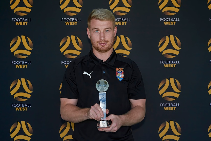 A man in an ECU Joondalup polo shirt holding a trophy, in front of a Football West background.