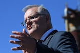 Close up of Scott Morrison talking and raising his hand.