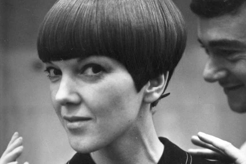 A close up, black and white image of a petite framed woman with a short bob cut.
