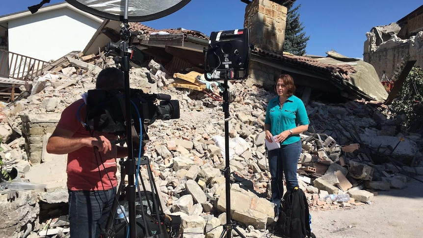 Millar and cameraman standing in rubble of a destroyed house.