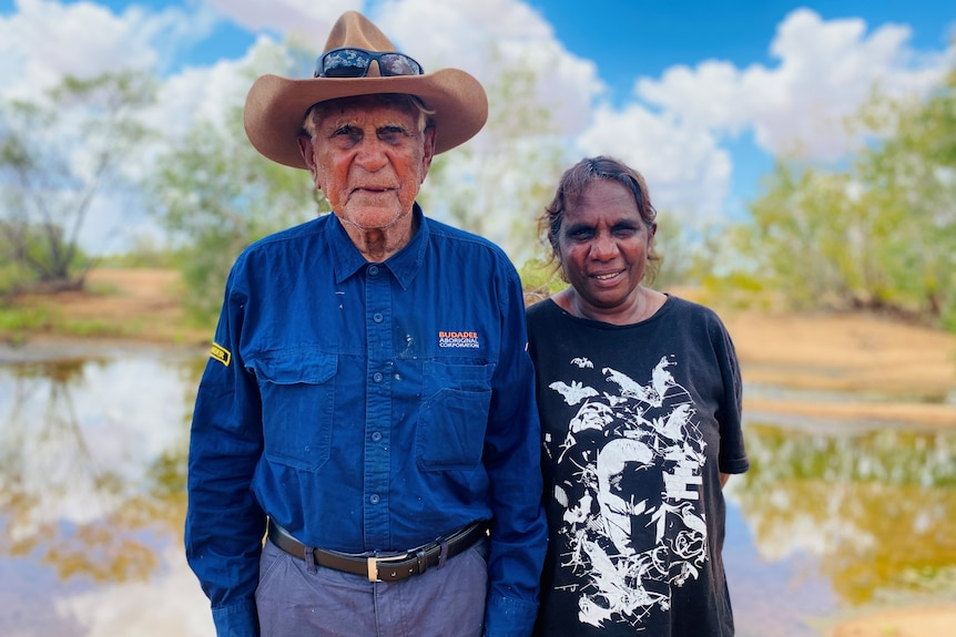 An elderly Indigenous man and his smiling daughter, standing in front of a waterway.