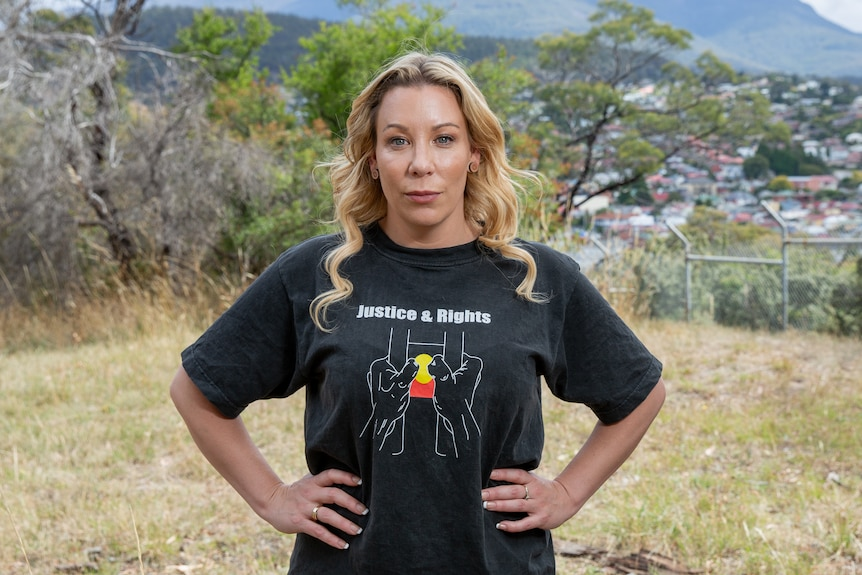 A woman poses for a photo with her hands on her hips in front of a mountain. She's wearing a t-shirt with the Aboriginal flag