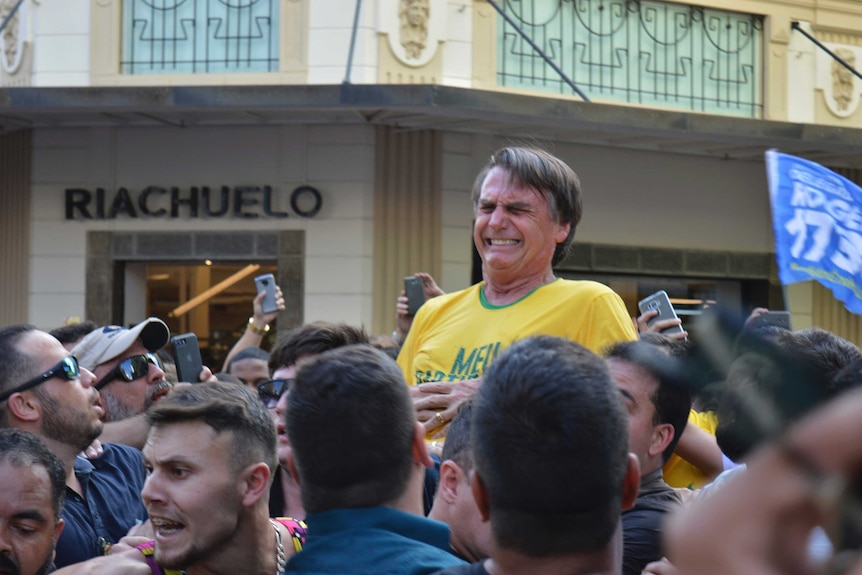 Jair Bolsonaro, who is being carried, grimaces right after being stabbed, with people all around him.