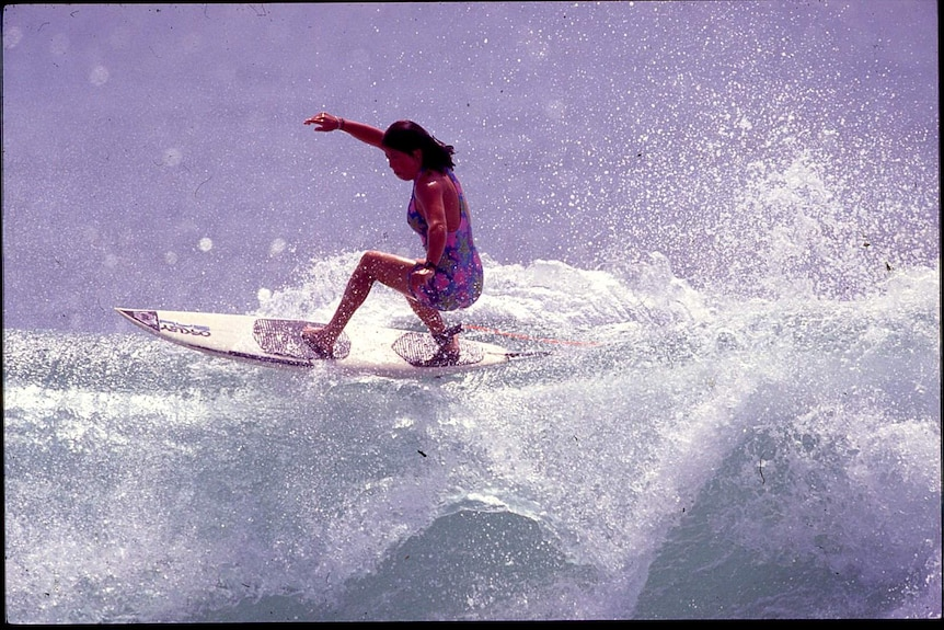 A woman with black hair and in purple swimmers surfing on top of a wave.