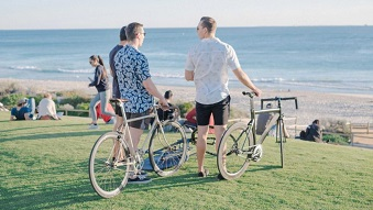 Three men look out to the ocean while holding their commuter bikes