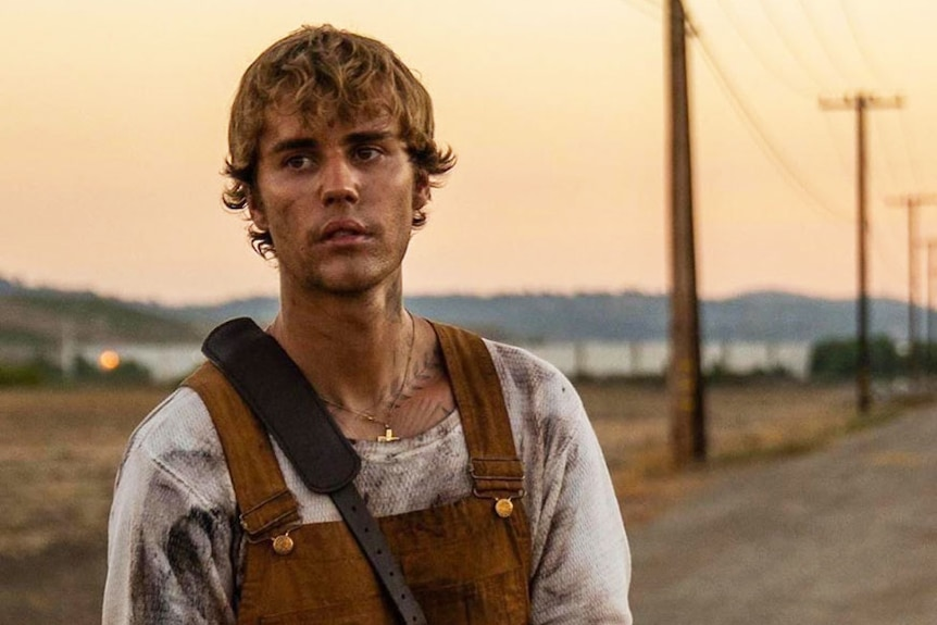 Justin Bieber in music video Holy, wearing overalls and looking dirty and sad.