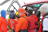 Australian Antarctic Division staff help load an ill expeditioner into a helicopter in Antarctica.