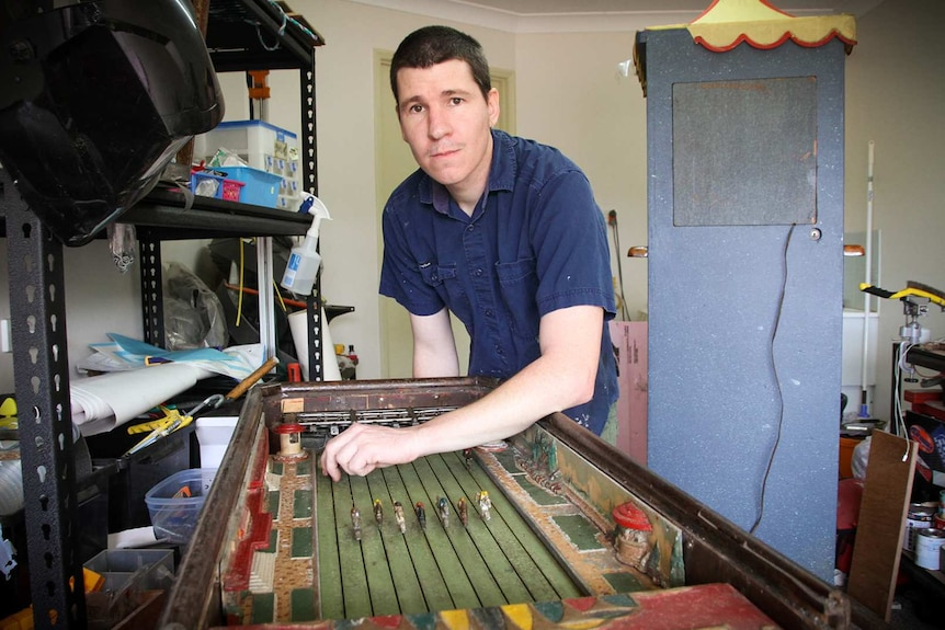 Repairer Jason Coultis stands over his arcade horse racing gambling game he restored.