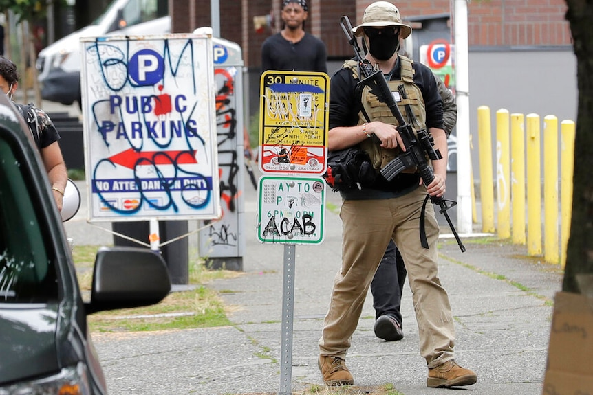 A man carrying an assault rifle while wearing a bulletproof vest, sunglasses, facemask and a hat walks along a Seattle street.