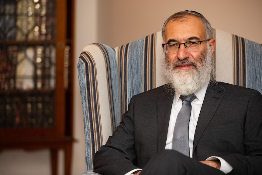 A close-up shot of Rabbi Marcus Solomon posing for a photo while sitting down in an armchair indoors.