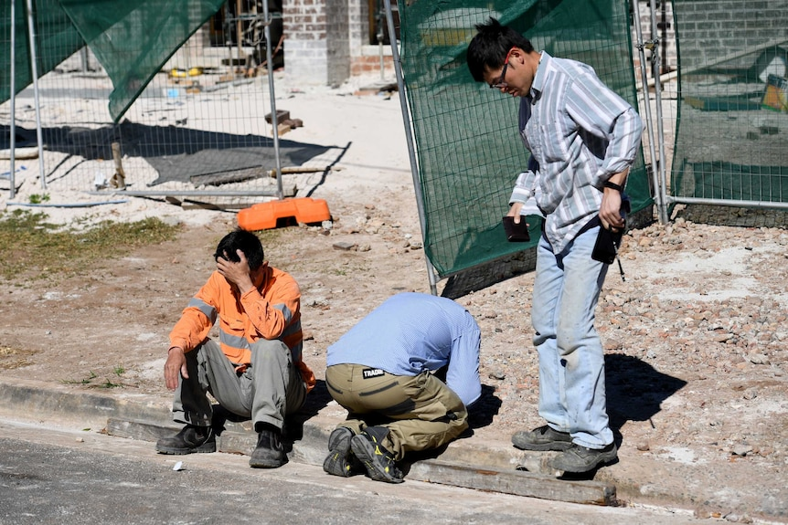 Workers from a nearby worksite gather following a man's death on a building site in Carlingford, northwest of Sydney.