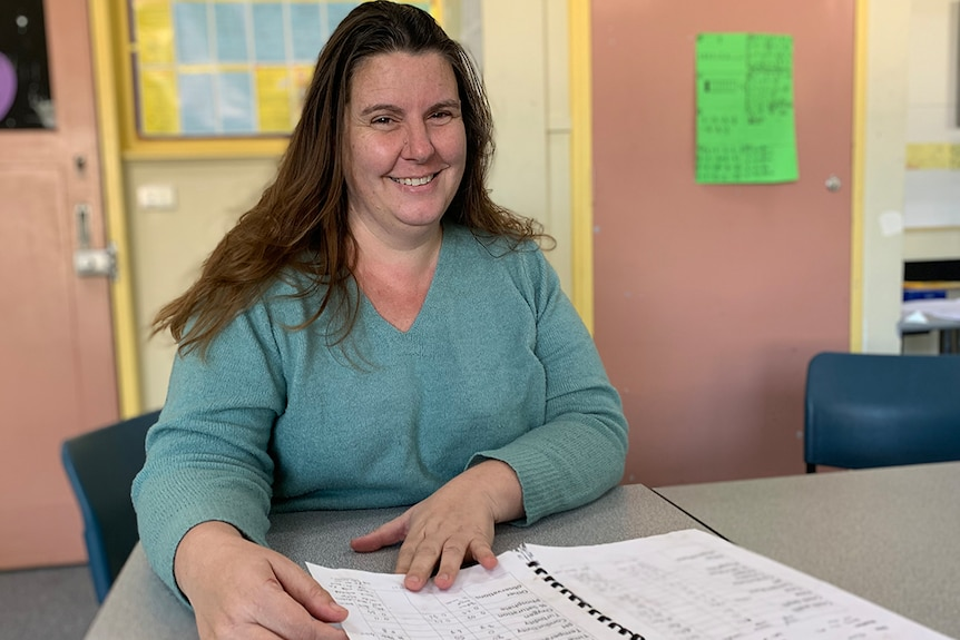 Woman sitting on a chair at a desk in a classroom, smiles at camera, with a notebook on desk in front of her.