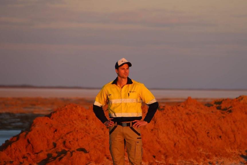 Man in high vis work shirt stands during sunset overlooking salt lake.