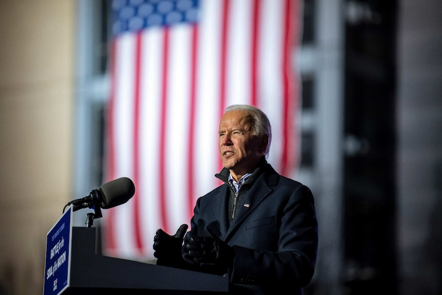 Joe Biden stands at a lecturn in front of an American flag as he gives a speech in Pittsburgh