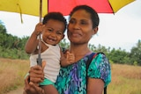 A woman holding a smiling baby under an umbrella