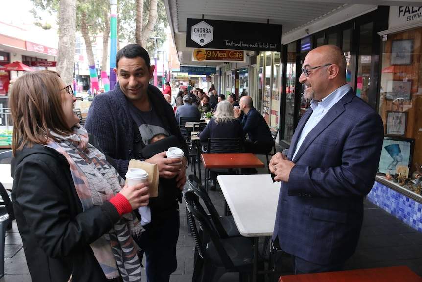 Two men and a woman standing on footpath with coffee cups talking.