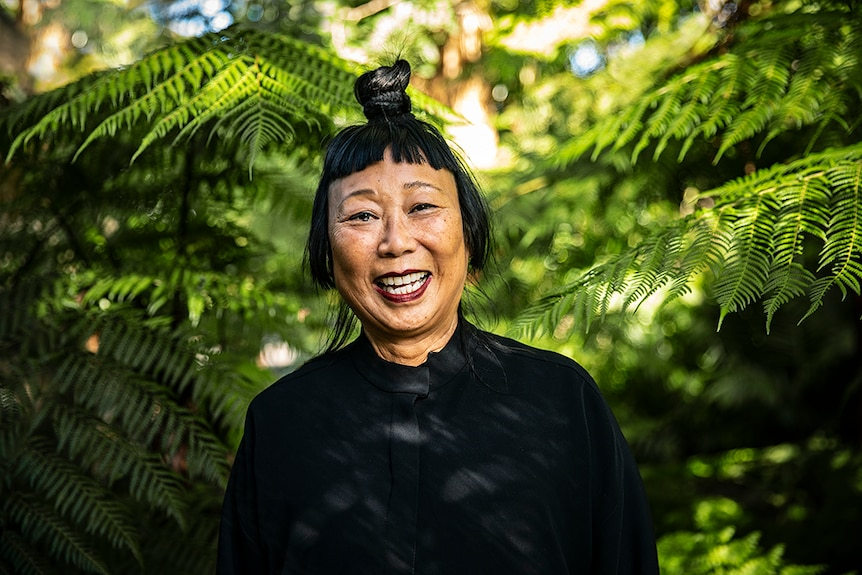 A woman with black hair tied up in top knot and Mao collar style jacket laughs in lush green outdoor area surrounded by ferns.