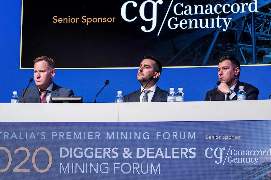 Three mining executives sitting behind a desk at a conference.