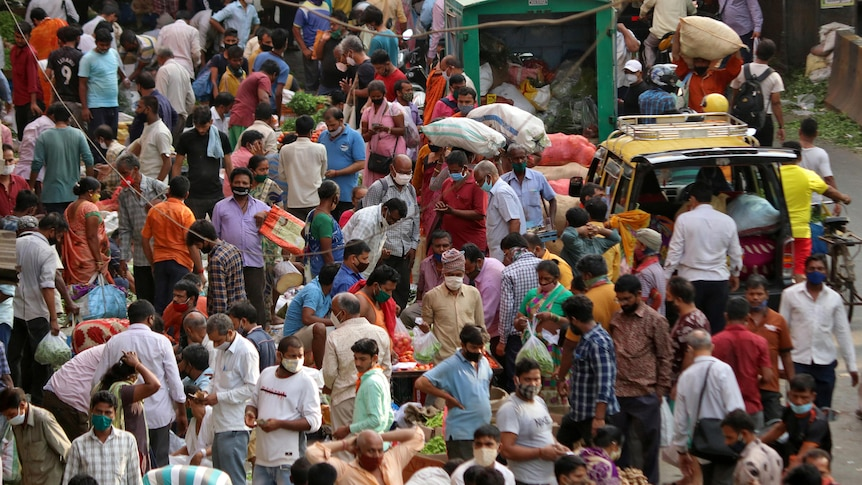 Dozens of people crowd a busy marketplace in India. Some people are wearing face masks.