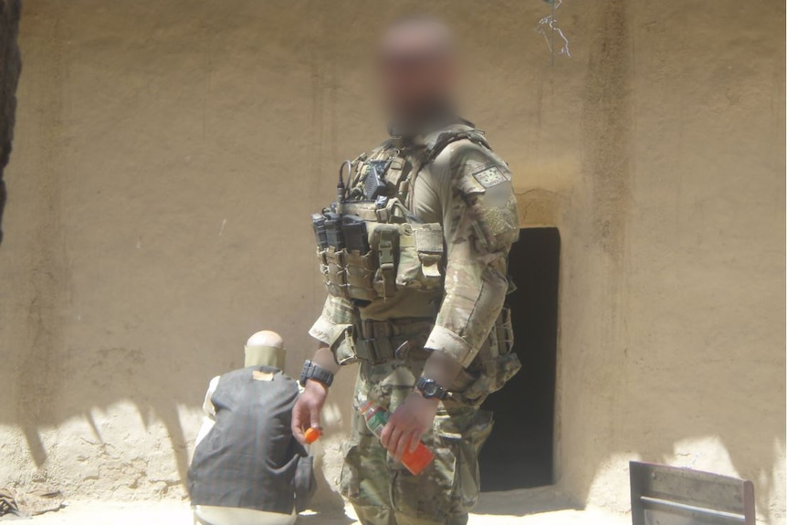 An Australian solder stands in front of an Afghanistan building.