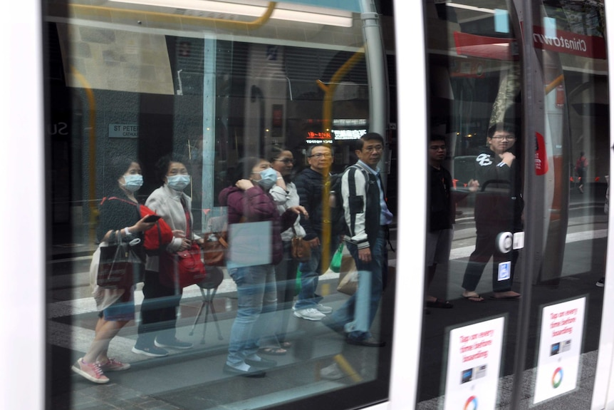 A group of people in the reflection of a light rail car's window, some are wearing face masks.