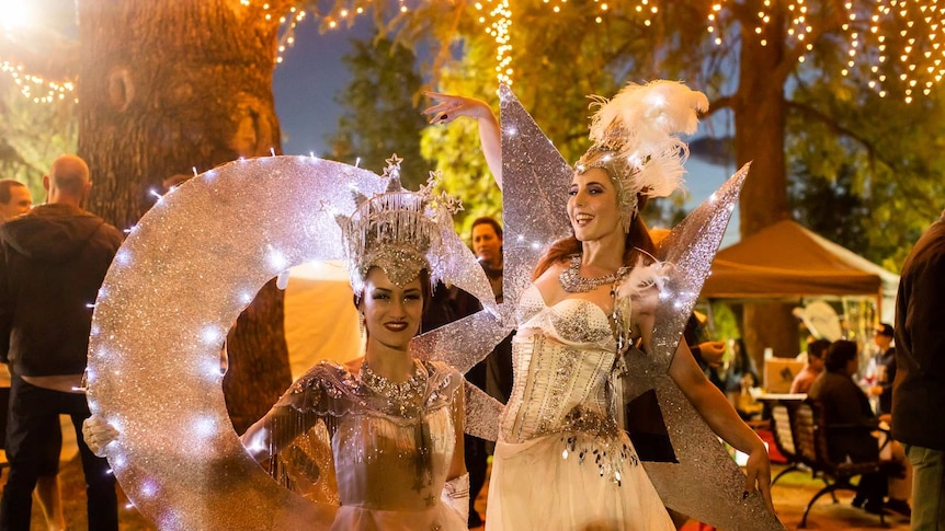 Two female dancers in elaborate silver costumes to represent a crescent moon and a star pose in a park at night.