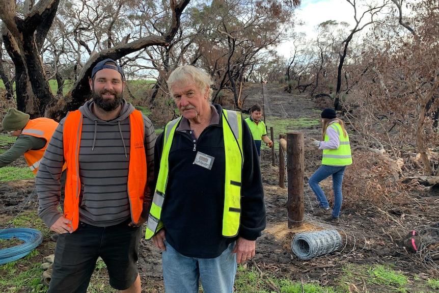 Blaze Aid volunteers Jack Tourlamain and Graham Norfolk stand in front of trees and wooden fence posts