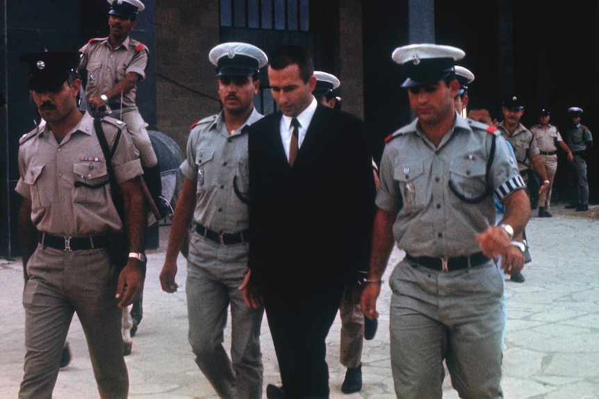 Police surround a suited Denis Rohan
