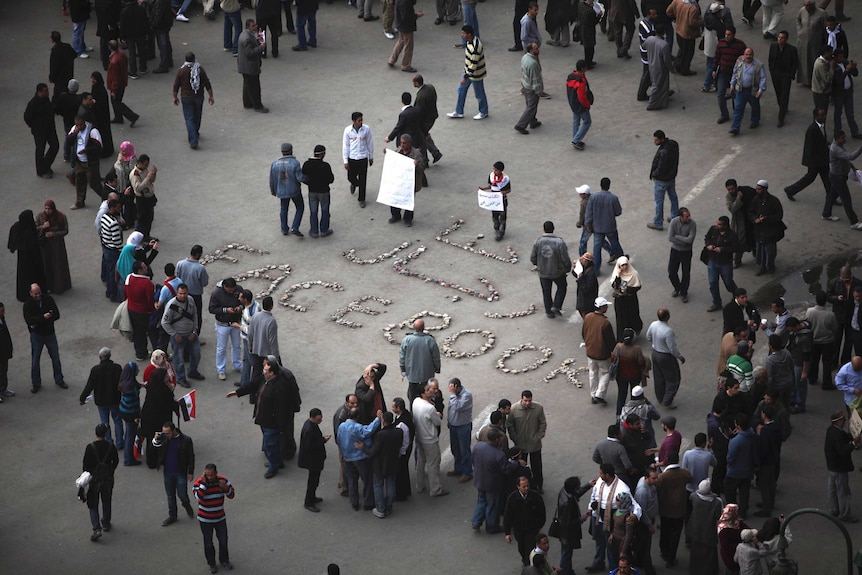 """""""We are the men of Facebook"""" is written on the ground as anti-government protesters gather in Tahrir Square."""