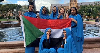 Seven women dressed in blue pose with a Sudanese flag in front of a fountain and cathedral in Sydney,