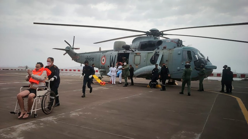 An Indian Navy helicopter in the background with a man being taken away in a wheelchair after rescue from the Arabian sea