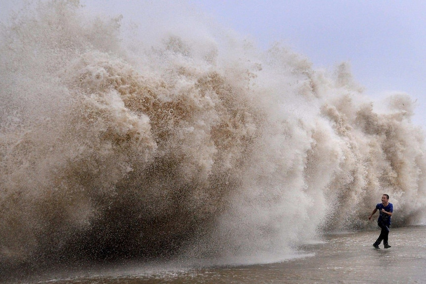 A man runs away from a huge wave pushed up by Typhoon Usagi.