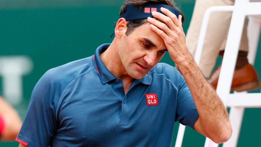 Roger Federer looks down, his hand taking off his bandana.