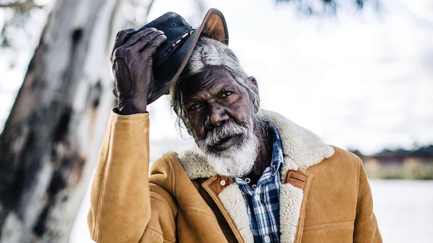 Actor David Gulpilil, an older Yolngu man in shearling coat taking off his akubra, in the documentary My Name is Gulpilil