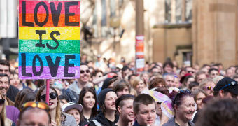 """Same-sex marriage activists march in the street during a rally in Sydney, with one holding a rainbow sign saying """"Love is love""""."""