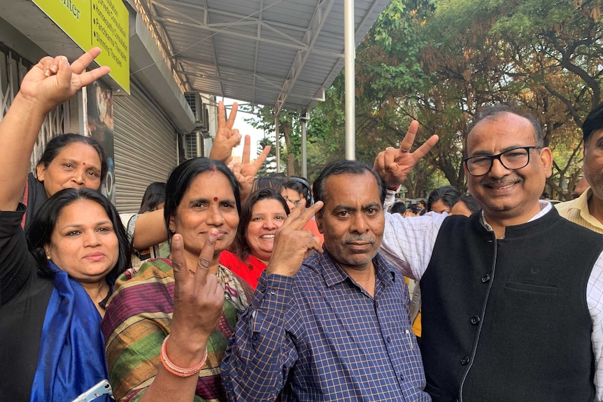 People in a street in India showing the peace sign with their fingers.