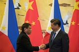 Rodrigo Duterte (L) and Chinese President Xi Jinping shake hands after a signing ceremony.