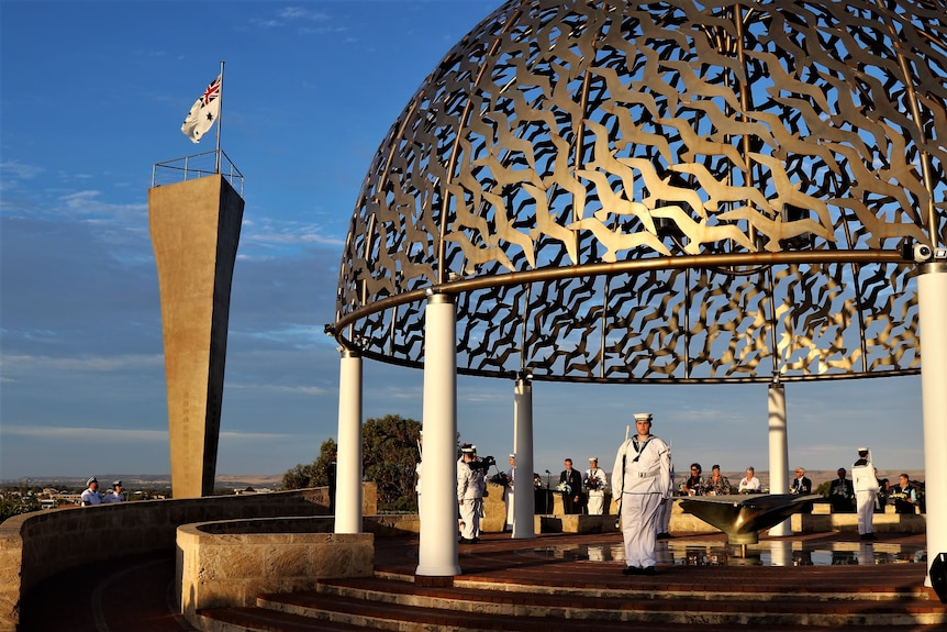 Navy personnel stand to attention under a copper-coloured steel dome atop round poles at the site of the HMAS Sydney II Memorial